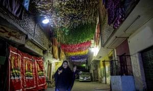 Una mujer camina por una calle decorada un día antes del mes sagrado del Ramadán, en el distrito de Imbaba de Giza, en Egipto.