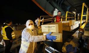 Los miembros del personal descargan donaciones médicas de China en el Aeropuerto Internacional de Argel.