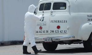 Un trabajador funerario se pone equipo de protección en la Ciudad de México, México, 25 de abril de 2020.