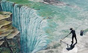 Un trabajador mantiene pinturas en 3D en el terreno en el área escénica de Longgang el 24 de abril de 2020 en Chongqing, China.