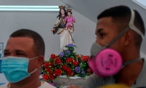 Los vendedores de pescado con máscaras se paran frente a una estatua de la Virgen del Carmen, patrona de los pescadores, en un mercado de mariscos en Panamá el 24 de abril de 2020.