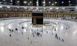 Los trabajadores de saneamiento desinfectan el área alrededor de la Kaaba en la Gran Mezquita de La Meca el primer día del mes sagrado islámico del Ramadán, en medio de prohibiciones sin precedentes de reuniones familiares y oraciones masivas debido a La pandemia de coronavirus.