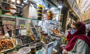 Un cliente con una máscara facial y guantes de plástico, debido a la pandemia del coronavirus Covid-19, se encuentra en una cita en el bazar Tajrish en Teherán, la capital de Irán, el 25 de abril. 2020, durante el mes sagrado musulmán del Ramadán.