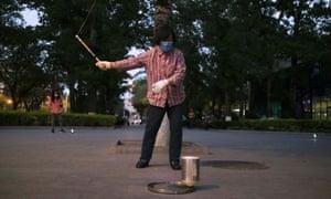 Una mujer con una máscara facial azota un trompo en una plaza en Beijing, China, 28 de abril de 2020.