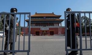 Los guardias de seguridad con una máscara facial se encuentran cerca de una entrada a la Ciudad Prohibida en Beijing, China, 20 de abril de 2020.