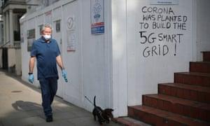 Un hombre con máscara protectora y guantes pasea a su perro frente a un graffiti que dice