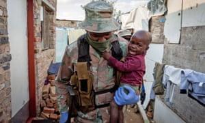 Un soldado de la Fuerza de Defensa Nacional de Sudáfrica lleva un bebé en su brazo en Johannesburgo, Sudáfrica, el 20 de abril de 2020.