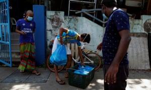 Los trabajadores migrantes recogen alimentos entregados por la organización no gubernamental Alliance of Guest Workers Outreach (AGWO).