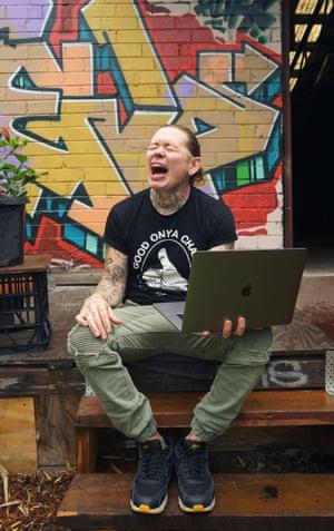 Nat con una computadora portátil en su regazo como si estuviera gritando