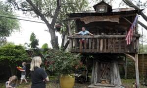 El Dr. Jason Barnes, arriba a la derecha, se sienta en la cabaña de sus hijos mientras su familia juega en su patio trasero el sábado 18 de abril de 2020, en Corpus Christi, Texas.