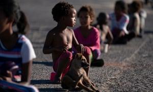Los niños sudafricanos se sientan a dos metros de distancia mientras esperan una comida en el barrio informal de Masincedane, beneficiario del programa de alimentación COVID-19 de 9 Miles Project y Hope Southern Africa (HOSA) en Ciudad del Cabo , en Sudáfrica, 28 de abril de 2020.