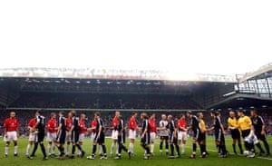 Los jugadores se dan la mano antes del saque inicial en Old Trafford.
