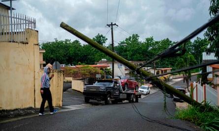 Un hombre guía una grúa debajo de un poste eléctrico caído después de que la tormenta tropical Isaias golpeara el área de Mayagüez en Puerto Rico la semana pasada.