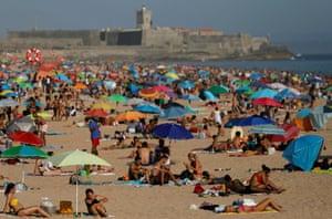 La gente disfruta del clima soleado en la playa de Carcavelos, cerca de Lisboa, en medio de la pandemia de coronavirus.