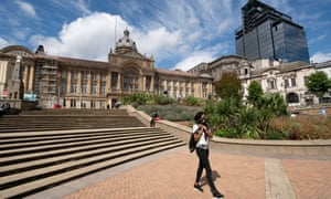 Un peatón con una máscara facial camina por el casi vacío centro de la ciudad de Birmingham.