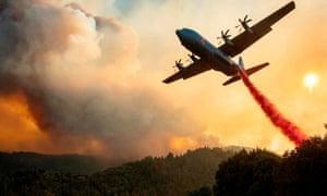 Un avión deja caer retardante de fuego sobre una cresta durante el incendio del Complejo Relámpago LNU en Healdsburg, California.