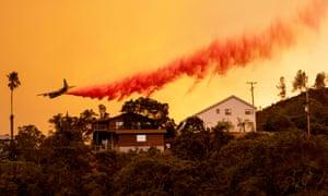 Un avión arroja retardante de fuego sobre casas en la zona plana española de Napa, California, mientras las llamas arden el 18 de agosto de 2020.