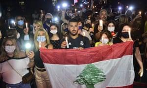 Los libaneses encienden velas mientras se reúnen alrededor del lugar de la explosión para conmemorar a los que perdieron la vida.