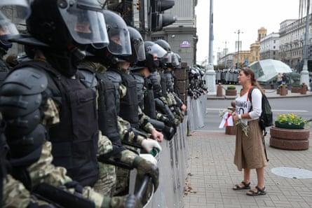 El domingo, una mujer sostiene flores y una bandera blanca, roja y blanca mientras hace cola para los agentes del orden en Minsk.