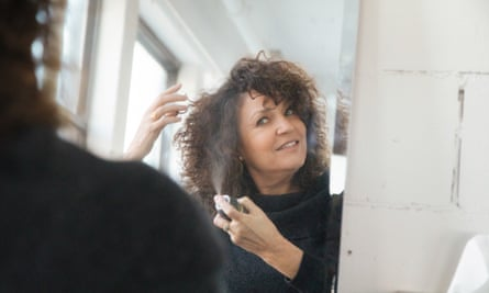 Mujer aplicando champú seco a su cabello en casa.