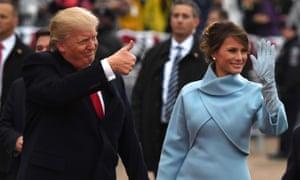 Donald Trump, vestido de negro, levanta el pulgar y Melania Trump, vestida con un abrigo azul y guantes, hace olas