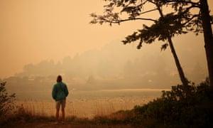 Una persona observa una ciudad en la costa del Océano Pacífico mientras el humo de los incendios forestales cubre un área cerca de Yachats, Oregon. El 8 de septiembre.