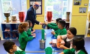Tim Roach, subdirector, usa un protector facial mientras supervisa a los niños de cuarto grado durante la pausa del almuerzo en la Academia Primaria Greenacres en Oldham, al norte de Inglaterra. Fotografía de Oli Scarff / AFP / Getty
