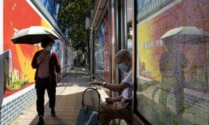 Los residentes usan máscaras para protegerse del coronavirus cerca de los paneles de propaganda del gobierno en una parada de autobús en Beijing el miércoles 2 de septiembre de 2020.