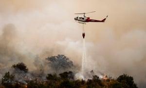 Un helicóptero deja caer agua sobre el incendio Bobcat, que arde en el Bosque Nacional Ángeles, cerca de Arcadia, California.