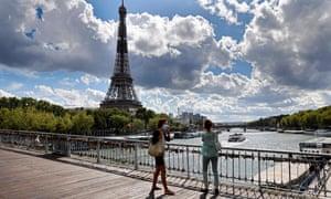 Dos mujeres con máscaras protectoras pasan por la Torre Eiffel en París la semana pasada