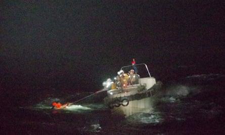 Oficiales de la Guardia Costera japonesa rescatan a un miembro de la tripulación del carguero que se hundió en el suroeste de Japón