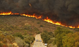 Los alguaciles de San Diego y los bomberos de la CDF actúan en Lyons Valley Road durante el incendio del valle el domingo