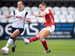 Caitlin Foord del Arsenal lanza el balón más allá de Anna Filbey del Tottenham Hotspur para marcar el tercer gol de su equipo.