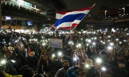 Los manifestantes ondean la bandera nacional tailandesa y hacen brillar las luces del teléfono en Bangkok