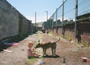 La hija de Mark, Pennie, con el perro Sonny en el callejón detrás de su casa en Darwen, Lancashire (2018)