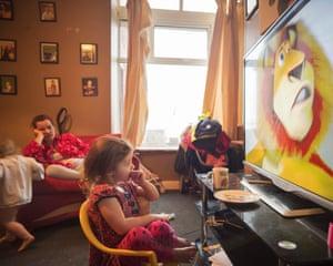 Poppie mira televisión con Emma y Pennie detrás, Darwen, octubre de 2018