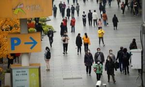 Personas con mascarillas caminan por una zona comercial en medio de la pandemia mundial de coronavirus en Beijing, China, el 16 de noviembre de 2020.