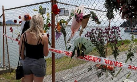 La gente mira un monumento en el puerto de Whakatane, tras la erupción del volcán White Island en Nueva Zelanda