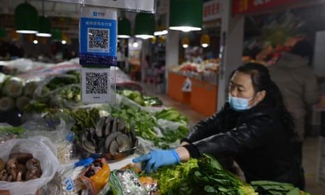 Un proveedor trabaja detrás de los códigos de pago QR en un mercado de Beijing.