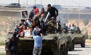 Sirios con retratos del presidente Bashar al-Assad abordan un vehículo de transporte de personal del ejército en mayo de 2011.