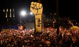 Los manifestantes libaneses ondean banderas nacionales durante las protestas contra el gobierno en noviembre de 2019.