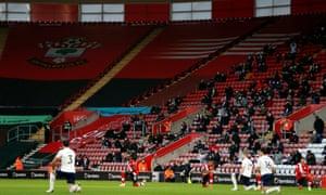 Los jugadores de Southampton y Manchester City se arrodillan mientras los fanáticos observan desde las gradas en St Mary's.