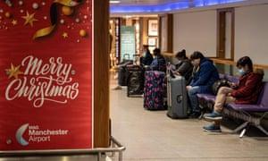 Los miembros del público en el aeropuerto de Manchester esperan junto a un cartel que desea a los pasajeros una Feliz Navidad