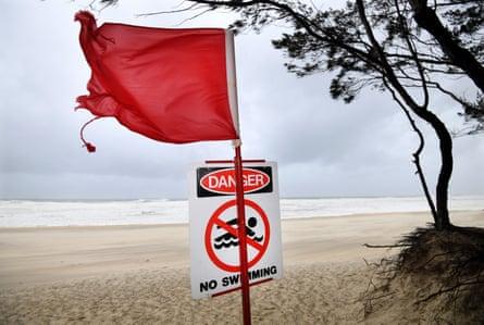 Una bandera roja y un letrero de no nadar se ven en Southport Beach en Gold Coast el domingo.