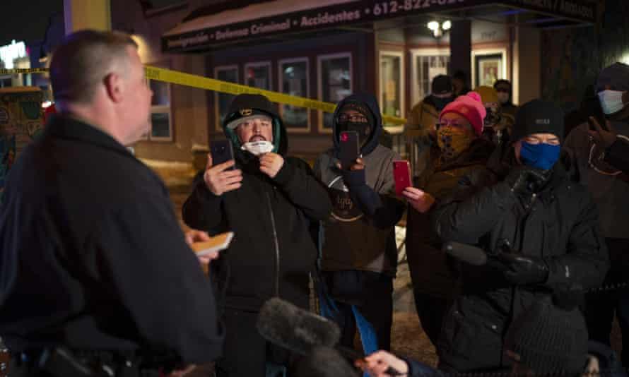 El portavoz de la policía de Minneapolis, John Elder, informa a los miembros de la comunidad y a otras personas sobre el tiroteo