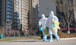 Los trabajadores llevan un contenedor de muestras de prueba de coronavirus fuera de una zona residencial en Shijiazhuang, provincia de Hebei, en el norte de China.