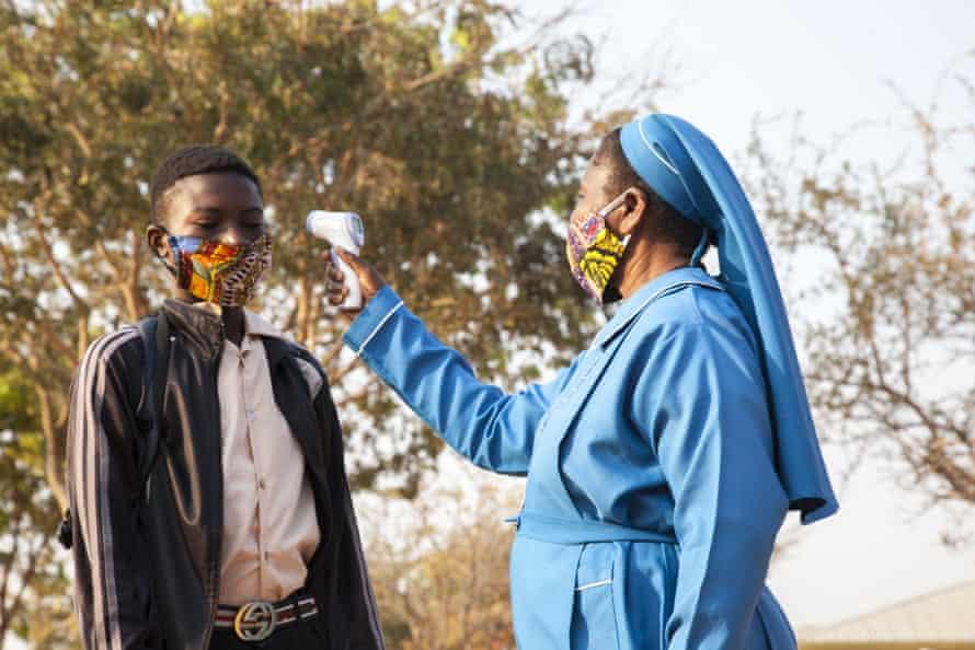 Un maestro lee las temperaturas en una escuela en Lusaka, Zambia. La investigación sugiere que el número de muertos en el país podría subestimarse en diez.