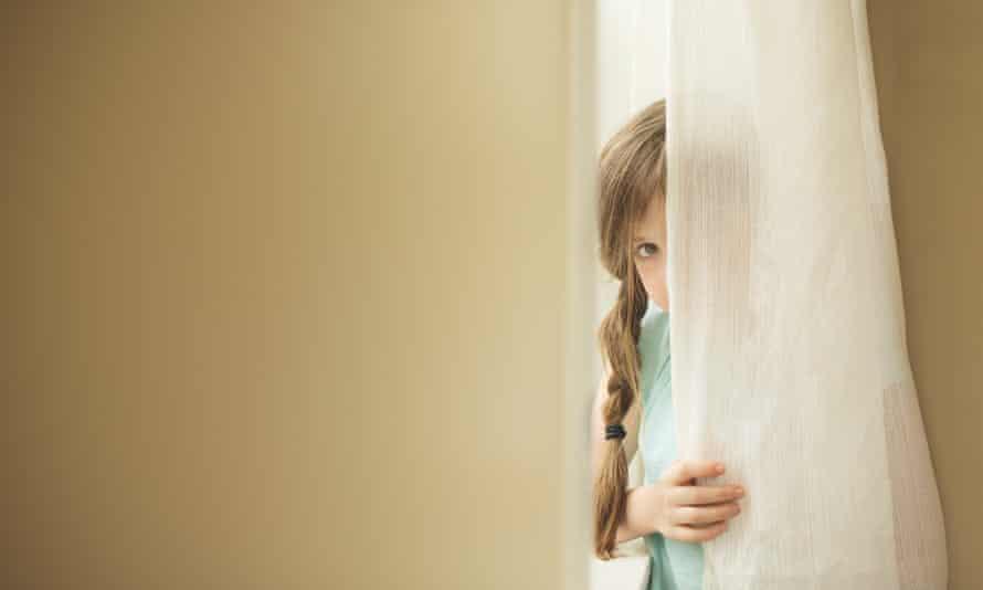 Chica tímida mirando alrededor de la cortina