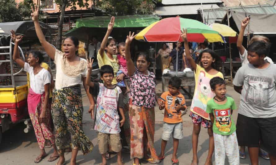 La gente saluda con tres dedos mientras observa a los manifestantes antigolpistas marchar por Mandalay el domingo 14 de marzo.