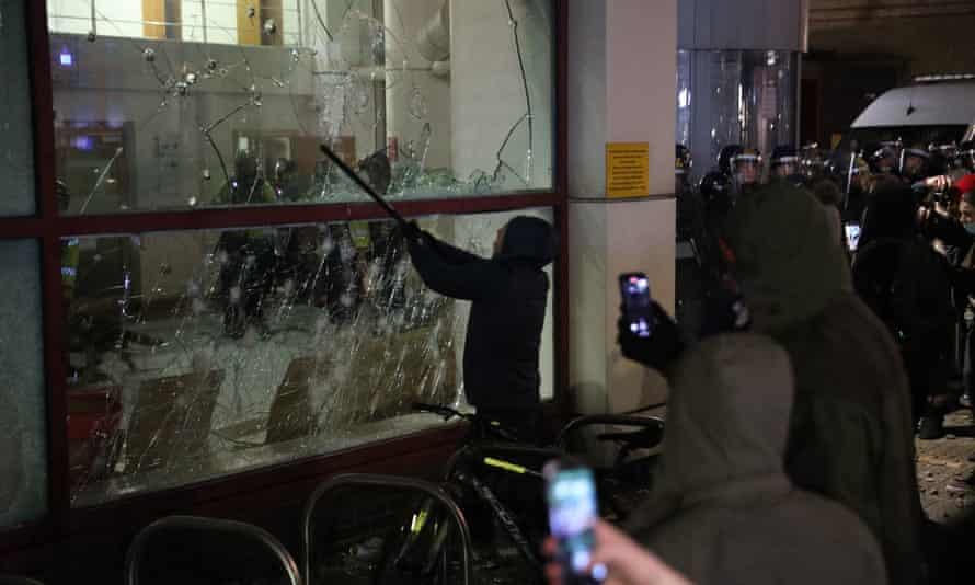 Un manifestante rompe una ventana en la comisaría de Bridewell.